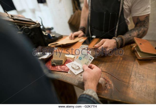 Customer paying with British Pounds in leather shop - Stock Image