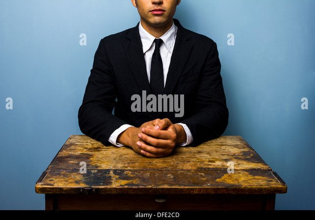 Young businessman is sitting at an old desk with his hands folded - Stock Image