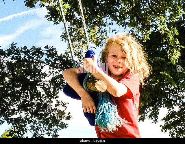 Young boy on home made swing in a park - Stock Image