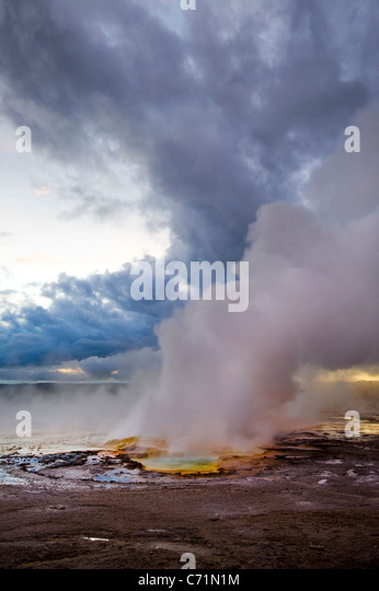 The Clepsydra Geyser erupts at sunset in the Lower Geyser Basin of Yellowstone National Park, Wyoming. - Stock Image