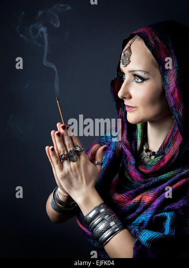 Woman wrapped in scarf holding incense stick in hands with Namaste gesture at dark background - Stock Image