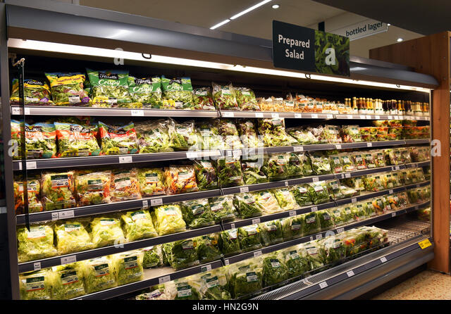 Pre-packed bags of salad on a refrigerated shelf in a supermarket - Stock Image