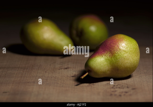 still life of three Comice pears on wood background - Stock Image