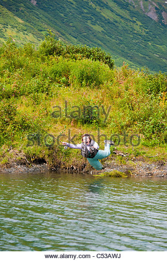 Humorous view of a fly fisherwoman falling into a lake with flyrod still in hand, Kenai Peninsula, Southcentral - Stock Image