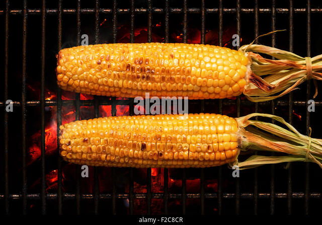 Whole Sweet Corn with leaves grilled on hot coal fire. Seen from above - Stock Image