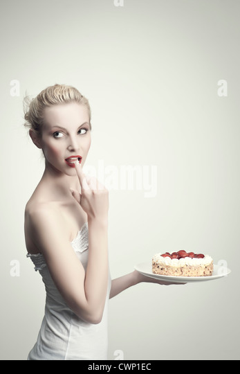 Young woman holding strawberry cake, licking cream off finger, portrait - Stock Image
