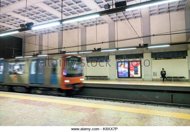 Portugal Lisbon Praca Marques de Pombal Metro Lisboa subway station public transportation platform moving train - Stock Image