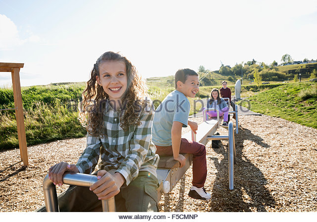 Carefree kids playing on long seesaw sunny playground - Stock Image