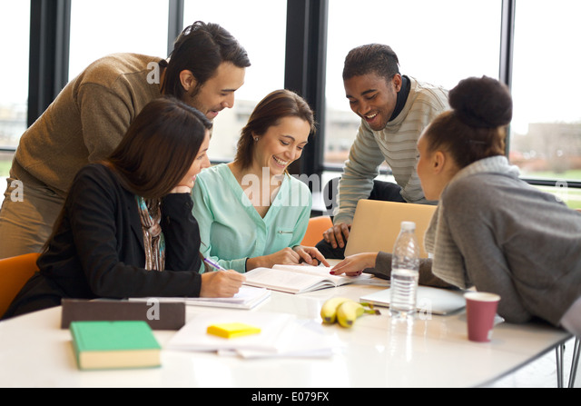 Group of happy young students in cooperation with their school assignment. Multiethnic young people sitting at table - Stock Image