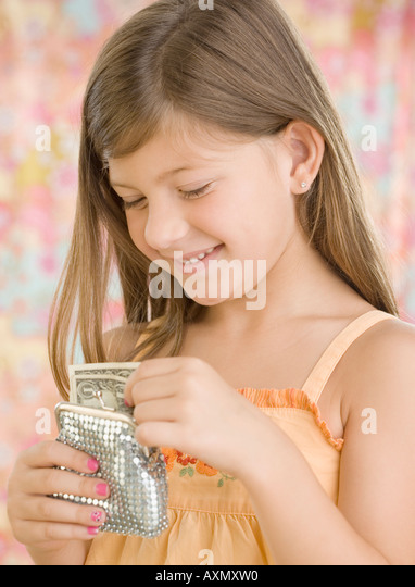 Young girl putting money in change purse - Stock Image
