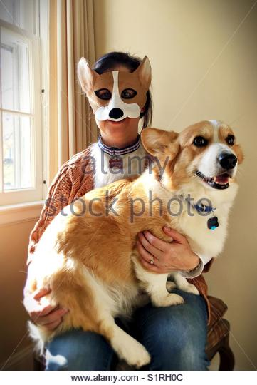 A woman in a dog costume, holding a dog. - Stock Image