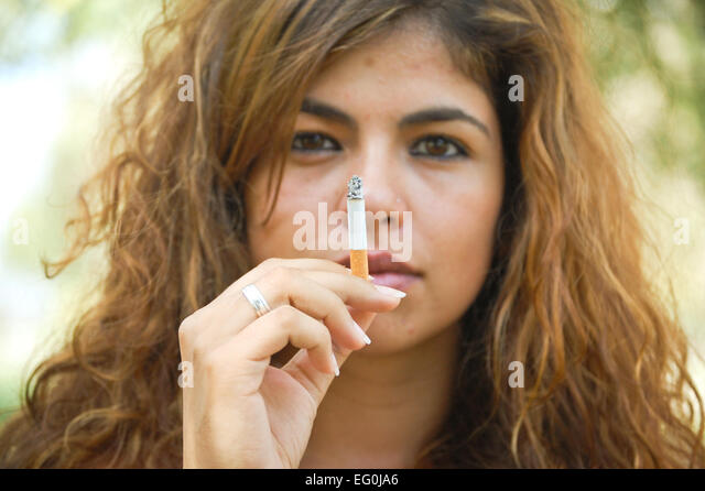 Portrait of long haired woman with cigarette - Stock Image
