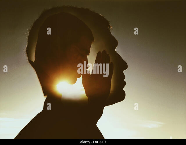 Digital composite of man praying - Stock Image