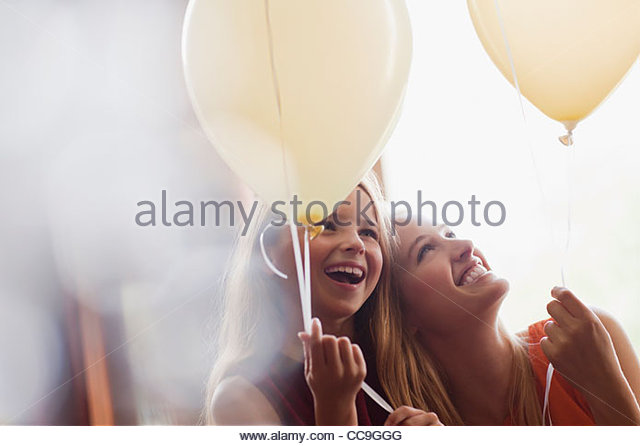 Laughing sisters with balloons - Stock-Bilder
