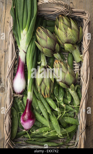 Fresh vegetables in a basket (artichokes,peas and red onions from Tropea) - Stock Image
