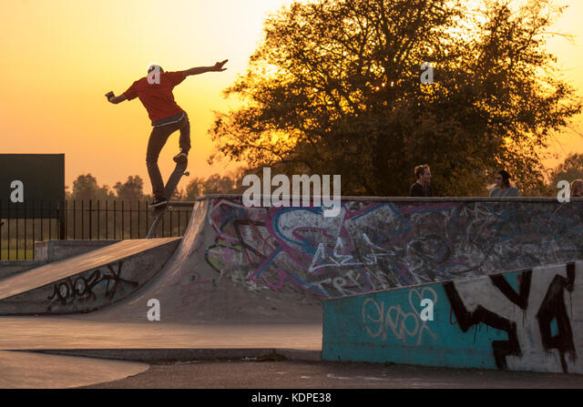Skateboarders, bmx and scooter riders at an urban skatepark in London as the sun sets - Stock Image