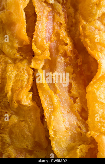 Chicken-Fried Bacon - Bacon slices dipped in a batter of whole dry milk and water, tossed in flour and deep fried. - Stock Image