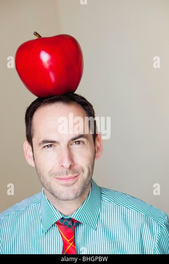 man with oversized apple on his head - Stock Image