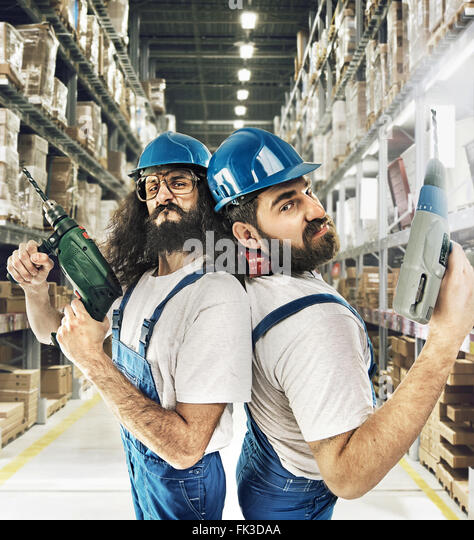 Portrait of two builders in a warehouse - Stock Image