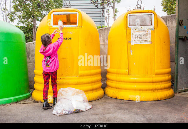 Containers of plastic for waste separation. Girl places plastic into a collector to recycle,recycling center - Stock Image
