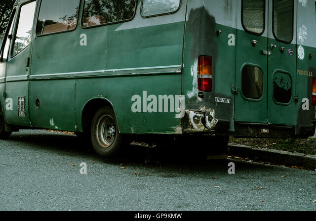 Green long wheelbase Ford Transit van jacked up on side of road for some repairs - Stock Image