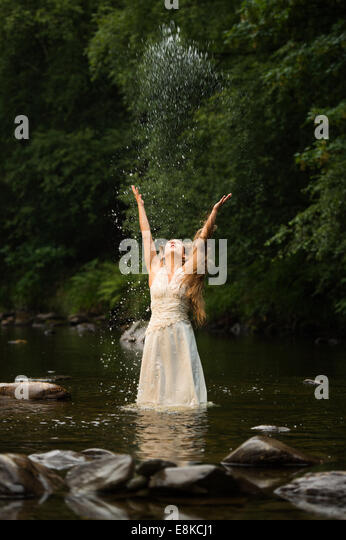 Trash the dress: a 'bride' wearing her wedding dress standing in a river throwing water into the air - Stock Image