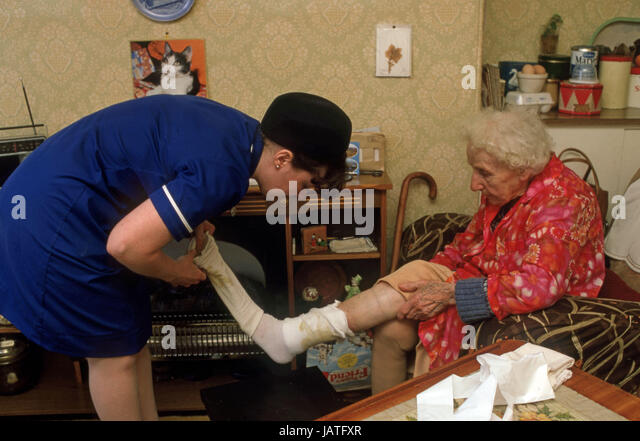 district nurse on a home visit cleaning an elderly woman's ulcerated leg - Stock Image