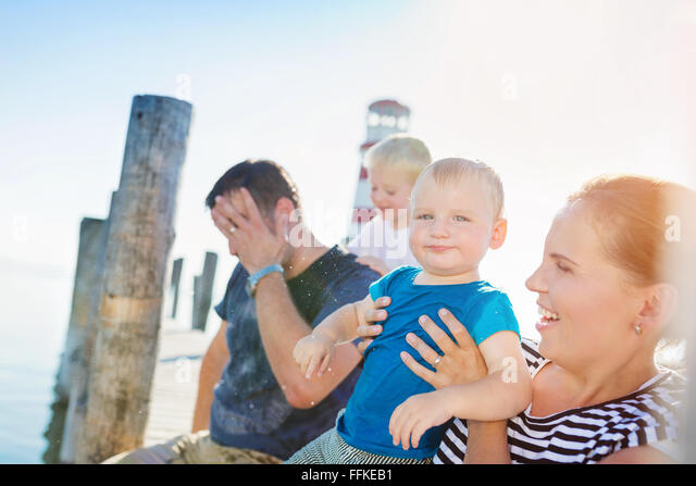 Family sitting on the pier, lighthouse, sunny summer day - Stock-Bilder