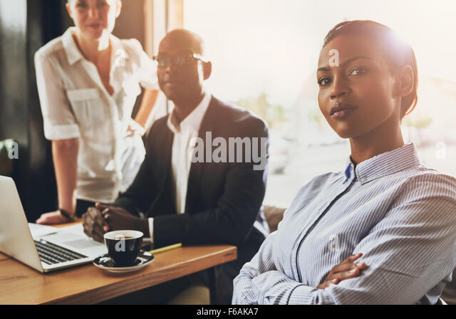 Confident young black business woman sitting in front of other business people - Stock-Bilder
