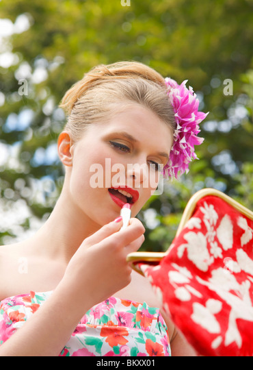 Close up of a young woman applying lipstick whilst holding her handbag - Stock Image