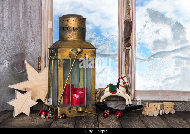 Nostalgic old christmas decoration with old toys and a old lantern with candles on the window sill. - Stock Image
