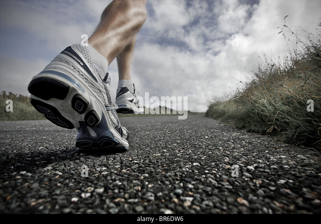 A close, low angle view of a male athlete running along a tarmac road with his large leg muscles showing - Stock Image