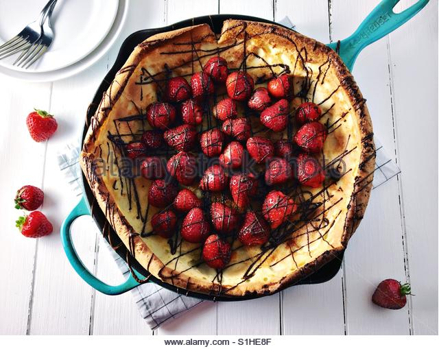 Strawberry dutch baby pancake with chocolate drizzle on white wood board. - Stock-Bilder