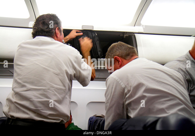 Texas Houston George Bush Intercontinental Airport IAH onboard flight from Charlotte passengers overhead luggage - Stock Image
