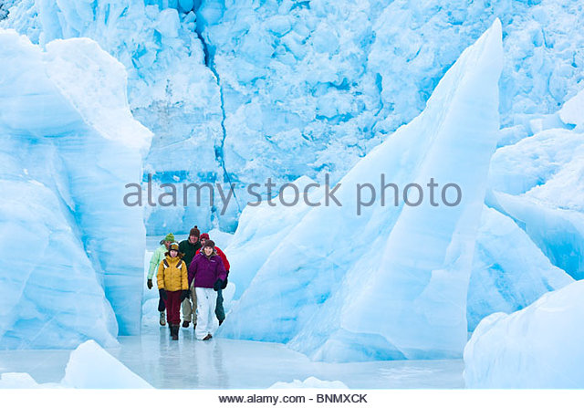 Group walking amongst icebergs frozen in Portage Lake at Portage Glacier, Chugach National Forest, Alaska - Stock Image