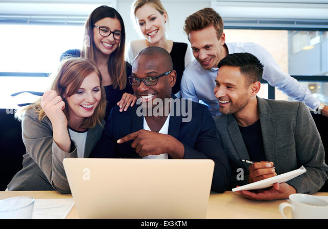 Black male executive smiling at camera with colleagues gathered around him and laptop - Stock Image