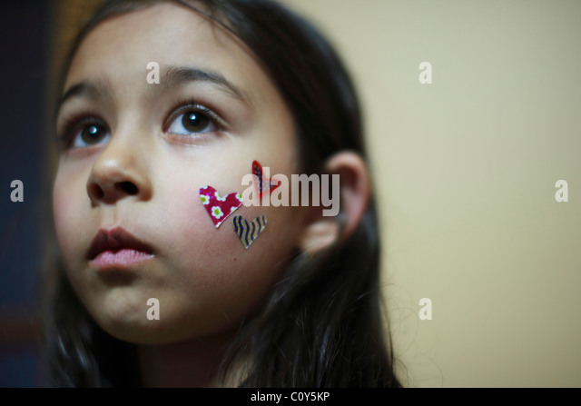 Girl with heart stickers on cheek - Stock Image