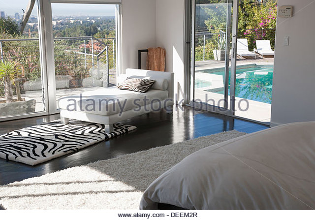 Interior of modern living room with glass walls - Stock Image