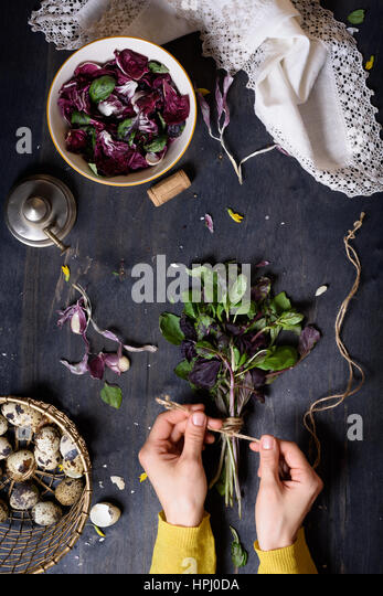 Herbs, gathered into a bunch and tied, over rustic table with salad and farm eggs. Overhead view. Healthy diet background. - Stock Image