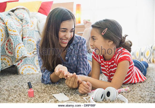Sisters painting fingernails in bedroom - Stock Image