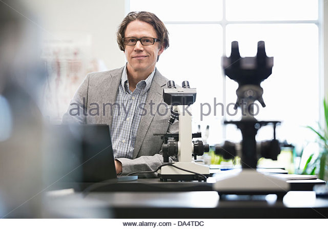 Portrait of male college professor leaning on table in science lab - Stock Image