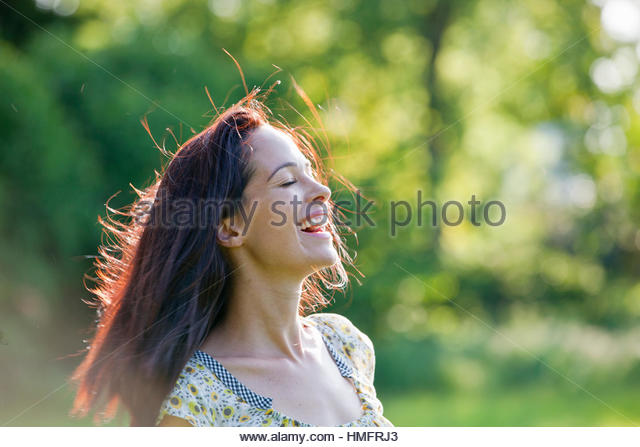 Carefree happy brunette woman in sunny summer park - Stock-Bilder