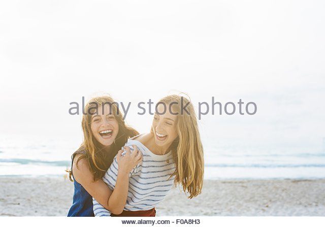 Portrait of two young female friends laughing at coast - Stock Image