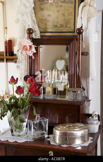 Red roses on dressing table with old perfume bottles - Stock-Bilder