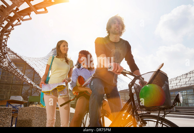 Germany, Bavaria, Munich, Three friends having fun at the Olympic Park - Stock Image