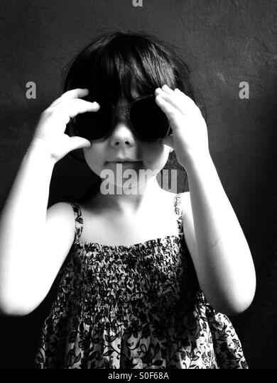 3-year old girl wearing sunglasses and summer dress. - Stock Image