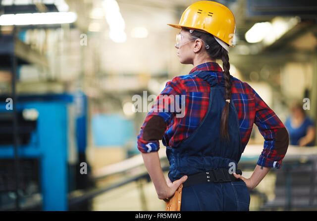 Female engineer in helmet controlling the process - Stock Image