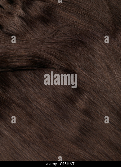 Brown natural human hair extensions background texture - Stock Image