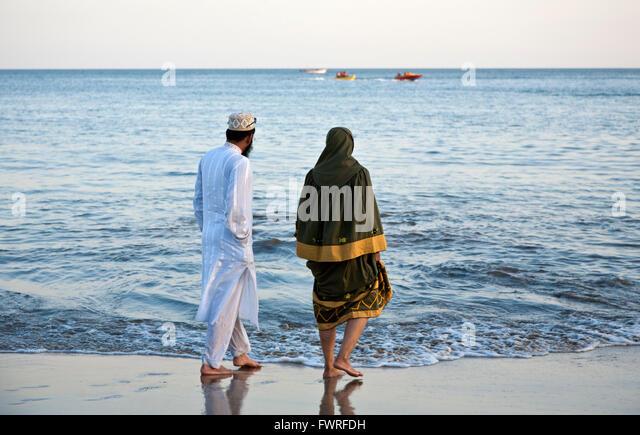 Muslim couple relaxing at Nagoya Beach. Diu. Union Territories of Daman and Diu. India - Stock Image