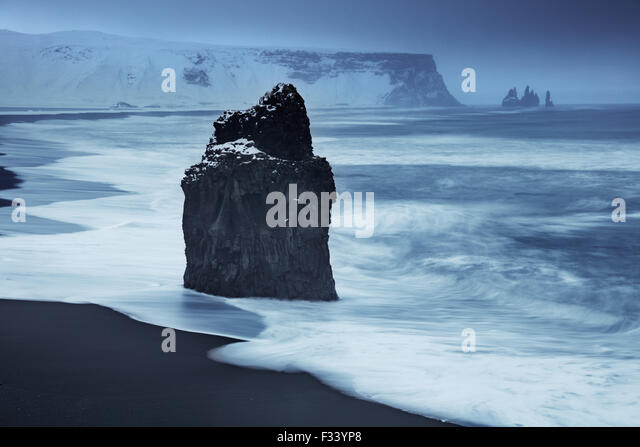 waves breaking on Reynisfjara with Reynisdranger beyond, Iceland - Stock Image